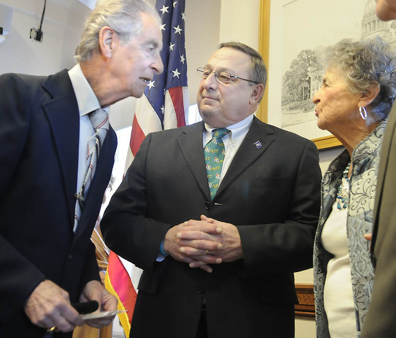 """Augusta resident Leo Pepin, left, and his sister, Madeline Patnaude, speak with Gov. Paul LePage after LePage signed a bill Monday designating a tune Pepin wrote, the """"Dirigo March,"""" as the state marching song at a Statehouse ceremony in Augusta."""
