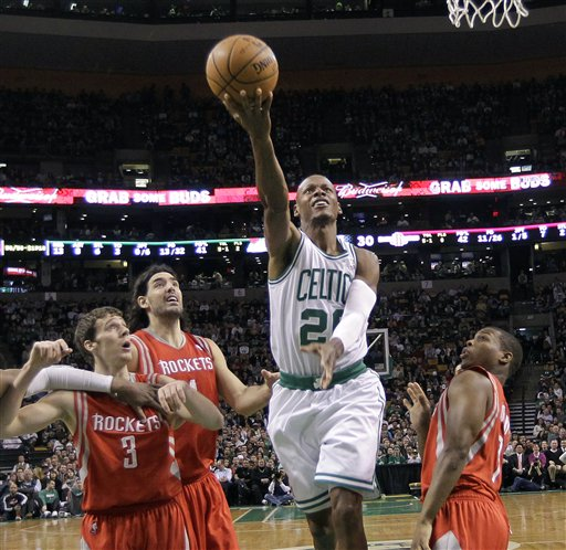 Boston Celtics guard Ray Allen (20) splits the defense as he goes to the hoop against Houston Rockets guard Goran Dragic (3), forward Luis Scola (4) and guard Kyle Lowry, right, during the first half Tuesday in Boston.