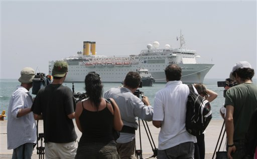 Members of the media and onlookers watch the Costa Allegra cruise ship as it is towed in Victoria harbor, Seychelles Island, today.