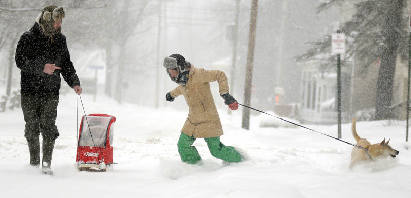 Meaghan Carlson, right, retrieves her dog Thursday as her husband, K.C. Carlson, tows their daughter, 1-year-old Freya, through Gardiner during the snowstorm. The Carlsons were walking so Freya could good have a birthday visit with her grandparents.