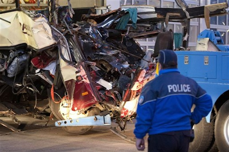 A police officer works at the wreckage of a tourist bus from Belgium at the accident site in a tunnel of the A9 highway near Sierre, western Switzerland, early Wednesday, March 14, 2012. A bus carrying Belgian students returning from a ski holiday crashed into a wall in a Swiss tunnel, killing 22 Belgian 12-year-olds and six adults, police said Wednesday. (AP Photo/Keystone, Laurent Gillieron)