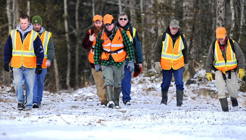 IN FORCE: Volunteer searchers hike through a field Thursday morning in Dresden near the Eastern River while looking for 12-year-old Micah Thomas.