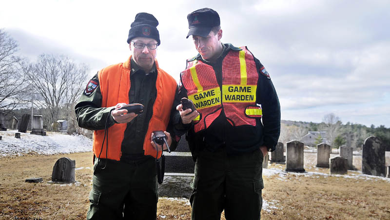 COMPARING NOTES: Game Wardens Steve Couture, left, and Justin Fowlie compare GPS data Thursday morning while searching near a cemetery in Dresden for 12-year-old Micah Thomas.