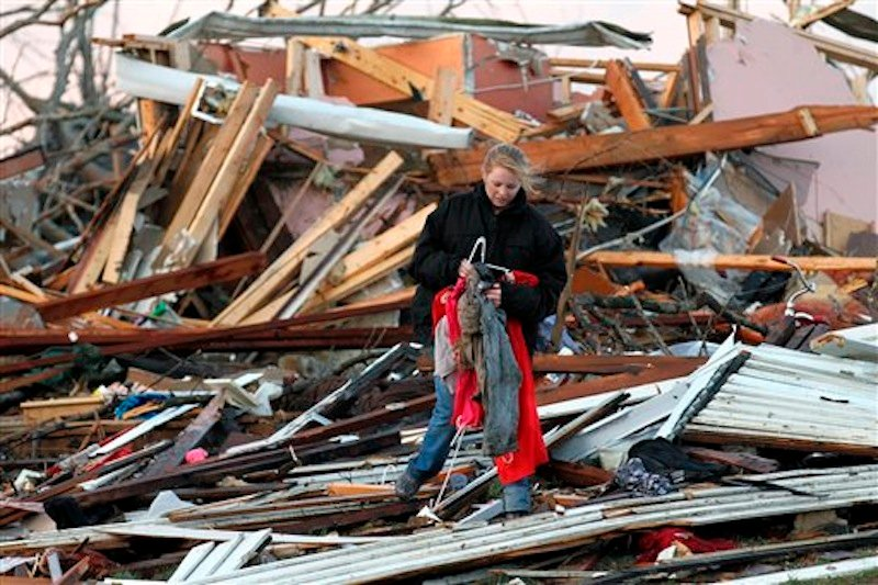 In this photo provided by SWAT Chasers via the Indianapolis Star, a woman salvages belongings from her home that was destroyed in Henryville, Ind., Friday, March 2, 2012, after a series of powerful tornadoes tore through southern Indiana, killing at least 32 people and leaving several small towns in ruin. (AP Photo/SWAT Chasers, Chris Bergin via the Indianapolis Star)