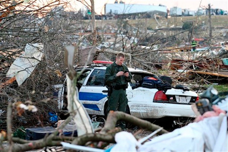 In this photo provided by SWAT Chasers via the Indianapolis Star, a police officer checks his phone while standing amid wreckage in Henryville, Ind., Friday, March 2, 2012, after a series of powerful tornadoes tore through southern Indiana, killing at least 14 people and leaving several small towns in ruin. At least one person was confirmed dead in hard-hit Henryville. (AP Photo/SWAT Chasers, Chris Bergin via the Indianapolis Star) NO SALES