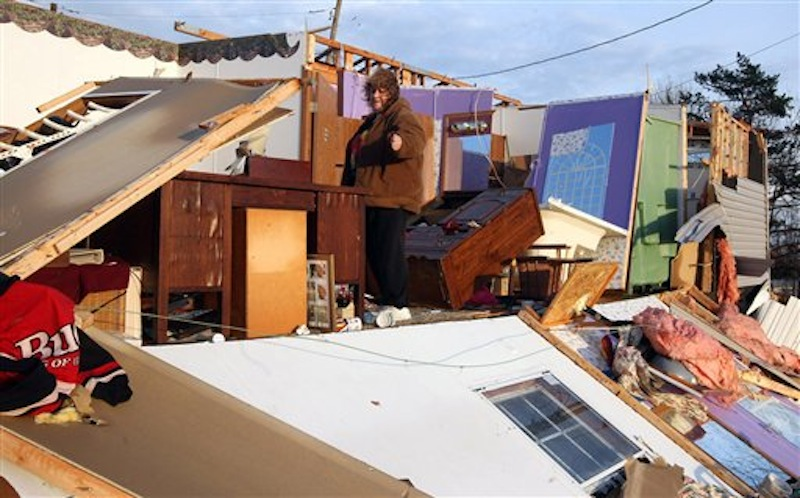 Judy Taylor surveys the damage to her trailer home on Carlisle Road, Piner, KY Friday March 2, 2012 after strong storms ripped through the area about 25 miles south of Cincinnati, OH. (AP Photo/The Enquirer)