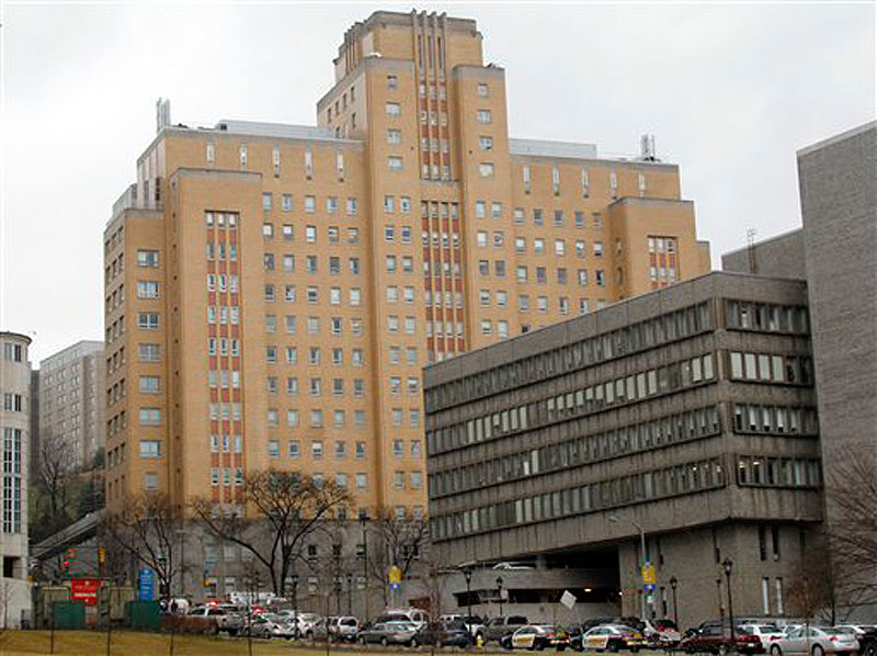 Police line O'Hara street near the front entrance to the Western Psychiatric Institute and Clinic, tan building, on the University of Pittsburgh campus on Thursday, March 8, 2012 in Pittsburgh. Two people died and seven were injured after a gunman open fired in the clinic. (AP Photo/Keith Srakocic)