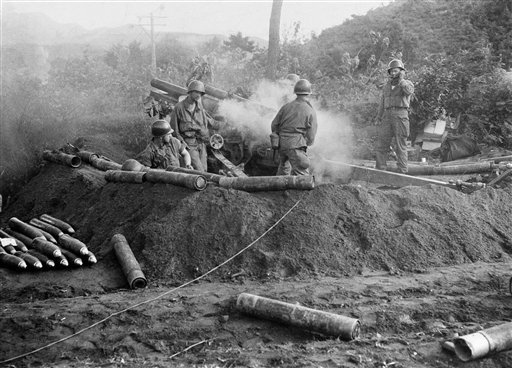 In this July 10, 1950, photo, American GIs fire a 105 mm Howitzer in action against North Korean invaders somewhere in Korea.