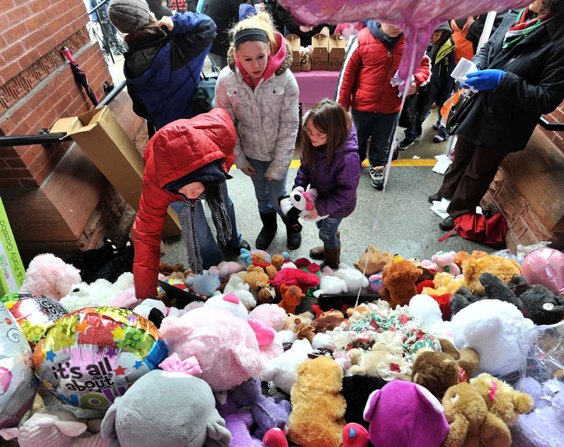 Photo by Michael G. Seamans Ashley-Ann Ferris, left, places a teddy bear on the steps of the Waterville City Hall with her cousin Skylar Starbird, 12, center, and daughter Hailie Hotham, 7, during a vigil for missing toddler, Ayla Reynolds, at Castonguay Square in downtown Waterville Saturday.