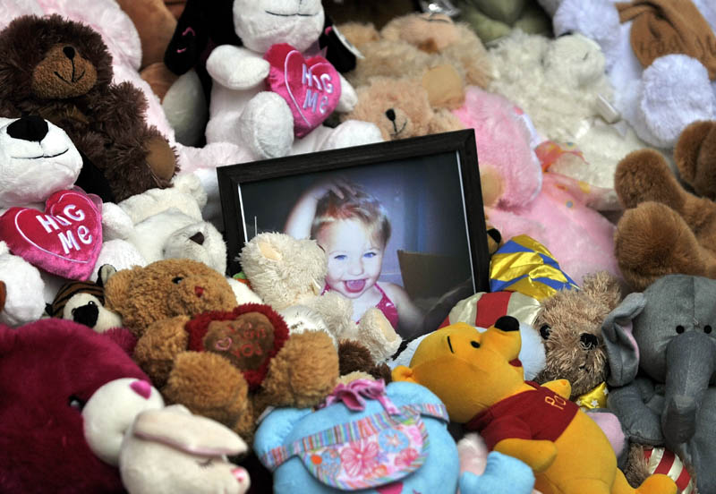 MISSING: A picture of Ayla Reynolds sits among a shrine of teddy bears on the steps of Waterville City Hall during a vigil for the missing toddler at Castonguay Square in downtown Waterville on Saturday.