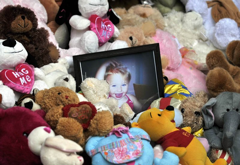A picture of Ayla Reynolds sits among a shrine of teddy bears on the steps of the Waterville City Hall during a vigil for missing toddler, Ayla Reynolds, at Castonguay Square in downtown Waterville Saturday.