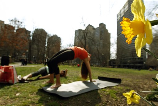 Danielle DelVecchio, left, takes pictures of Aileen Palmer as Palmer does yoga near the flowers in bloom in Rittenhouse Square in Philadelphia on Tuesday.