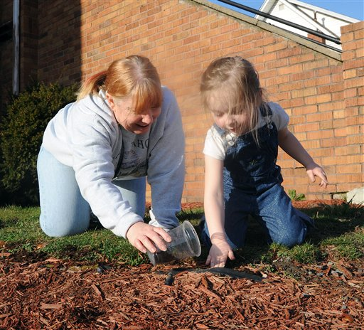 Debbie Sailor, left, helps 4-year-old Haedyn Scrannage plant tulip and daffodil bulbs around the Fairmont Free Methodist Church in Fairmont W.Va., on Tuesday. With temperatures climbing into the lower 70s for the first time this season it was a perfect day for planting.