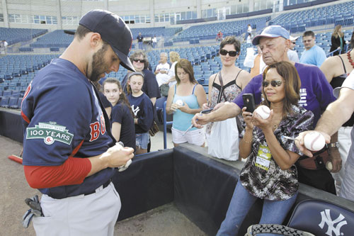 SURREAL: Boston's Dustin Pedroia signs autographs for fans before a spring training game against the New York Yankees on Tuesday at Steinbrenner Field in Tampa, Fla. Yankees fans — many of whom visited from the New York area — clamored for the Red Sox second baseman instead of shouting obscenities at him.