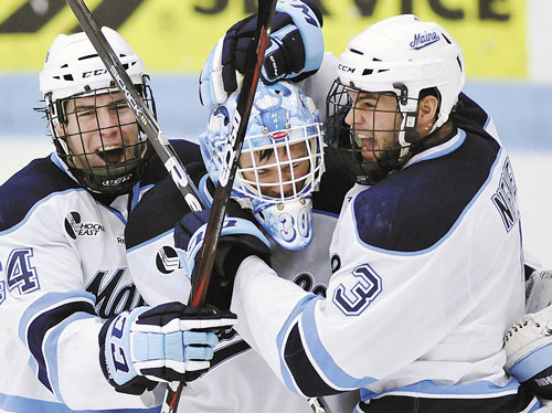 WE DID IT: Maine goalie Dan Sullivan, center, celebrates with Ryan Hegarty, left, and Mark Nemec after defeating Merrimack in a Hockey East quarterfinal game Sunday in Orono.