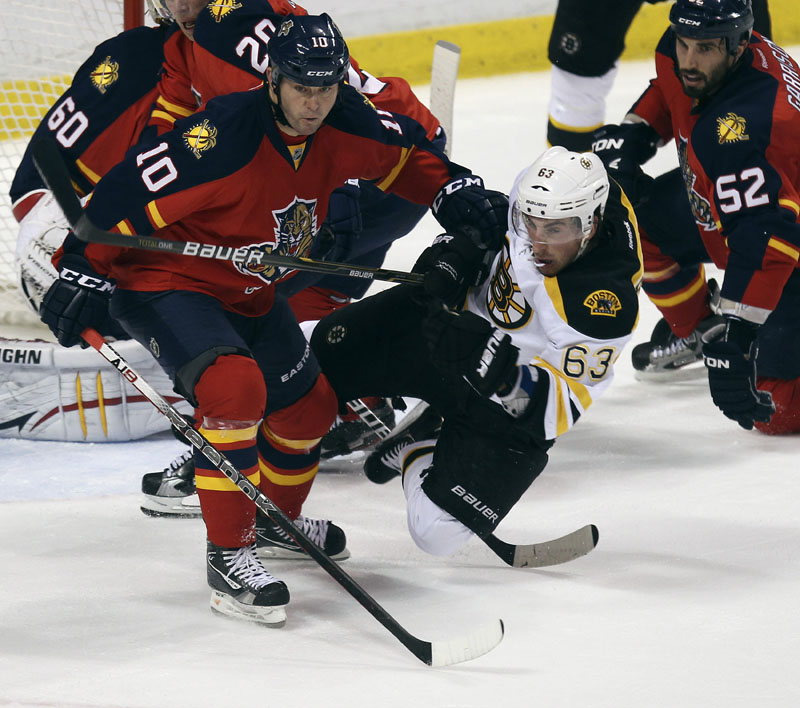 KNOCKED OUT: The Florida Panthers' John Madden, left, and Boston Bruins' Brad Marchand battle for puck during the second period Thursday night in Sunrise, Fla. Florida scored three goals during that period alone to pull away for a 6-2 victory.
