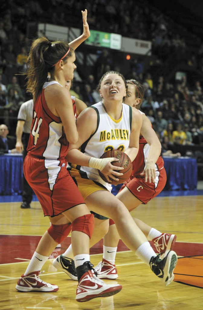John Ewing/Staff Photographer... Saturday, March 3, 2012....McAuley's Victoria Lux starts her move to the basket against Cony's #34, Melanie Guzman.