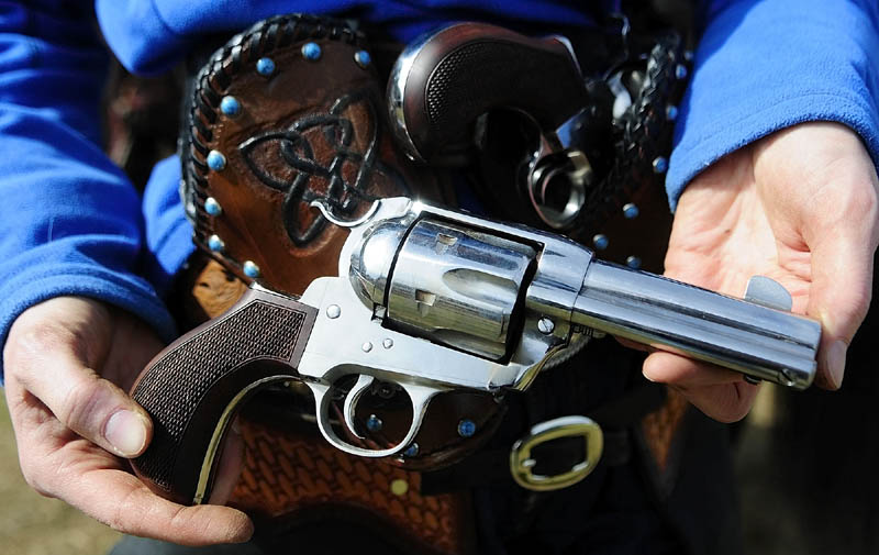 SIDE ARM: Sara Bell, of Warren, displays the Pony Express .45 caliber single action revolver she used in the Maine Cowboy Mounted Shooting Clinic on Saturday in West Gardiner. The sports uses .45 caliber single action revolvers like those used in the late 1800's. Single action revolvers must be cocked each time before firing by drawing the hammer back. They fire brass cartridges loaded with black powder and the heat blasting out of the barrel breaks the balloon target.