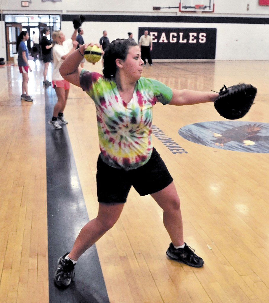 IT'S SPRING AGAIN: Messalonskee High School softball player Emily Nadeau, along with the rest of the pitchers and catchers, warm up during practice Monday in Oakland.