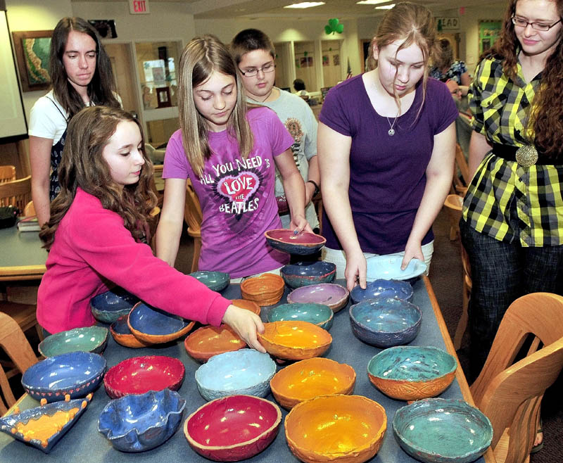 FILL 'EM UP: Skowhegan Middle School students unpack some of the 100 clay bowls they made that will be filled with soup and served with bread from 5:30-7:30 p.m. Friday to benefit area food cupboards. Students from left are Marinel Demmons, back, Samantha Joy, Elizabeth Jones, Andrew Todd, Mariah Bonneau and potter Yvonne Ballenbacher.