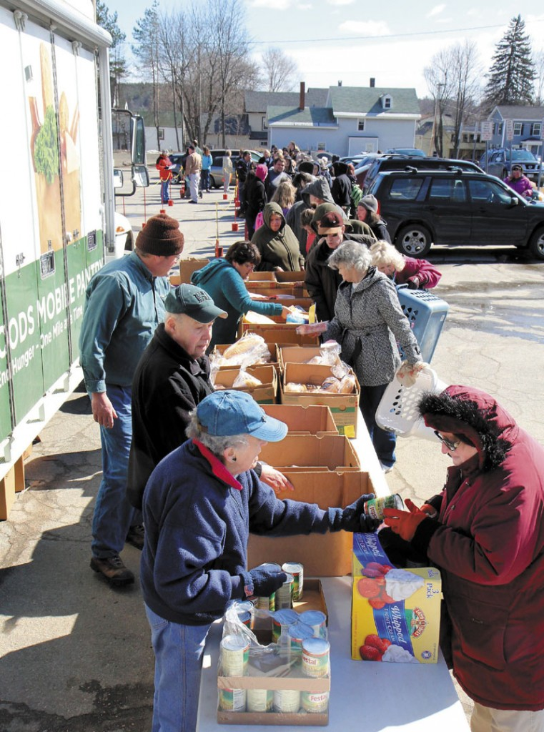 Volunteer Norma Shaw hands some food to Joanne Jones of Vassalboro on Friday in Augusta. The Augusta Food Bank used the Good Shepard Food Bank's food mobile, set up in a parking lot near Lithgow Library on State Street, to distribute 9,000 pounds of food to 347 families.