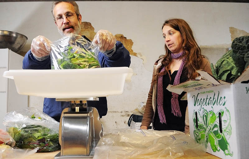 Dr. Harold Gram, left, and Sarah Miller, director of the Kennebec Local Food Initiative, weigh bags of greens as they split up large containers that came from farmers into orders for customers on market pickup day last week.
