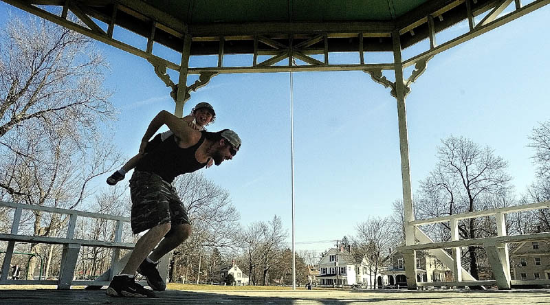 Michael McLaughlin gives his son a piggy-back ride out of the gazebo on a warm sunny Tuesday afternoon in Gardiner. They and many other people enjoyed the warm weather on the first day of spring playing on the playground and exploring the monuments at The Gardiner Common.