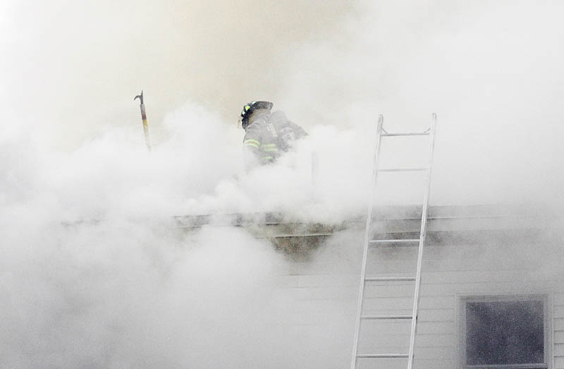 A firefighter cuts a hole in the roof to vent smoke from the blaze in a four-unit apartment building at 208 Hospital St. in Augusta on Friday. The Winthrop, Chelsea and Togus fire departments also responded to the fire that heavily damaged portions of the building.