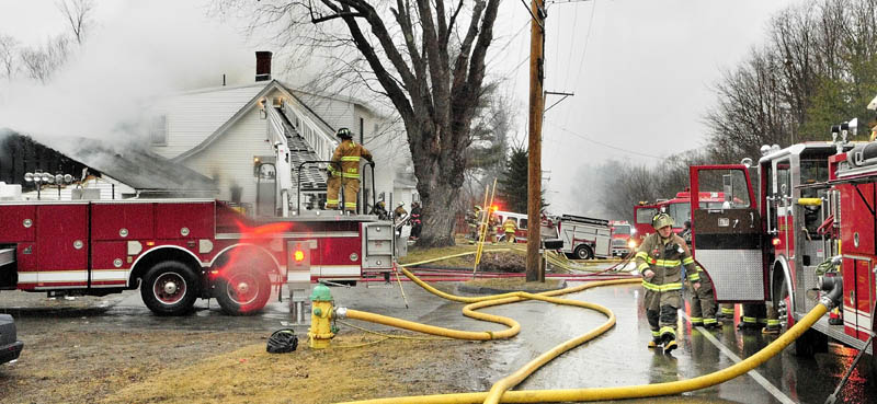Firefighters work at the scene of a fire in a four-unit apartment building at 208 Hospital St. in Augusta on Friday.