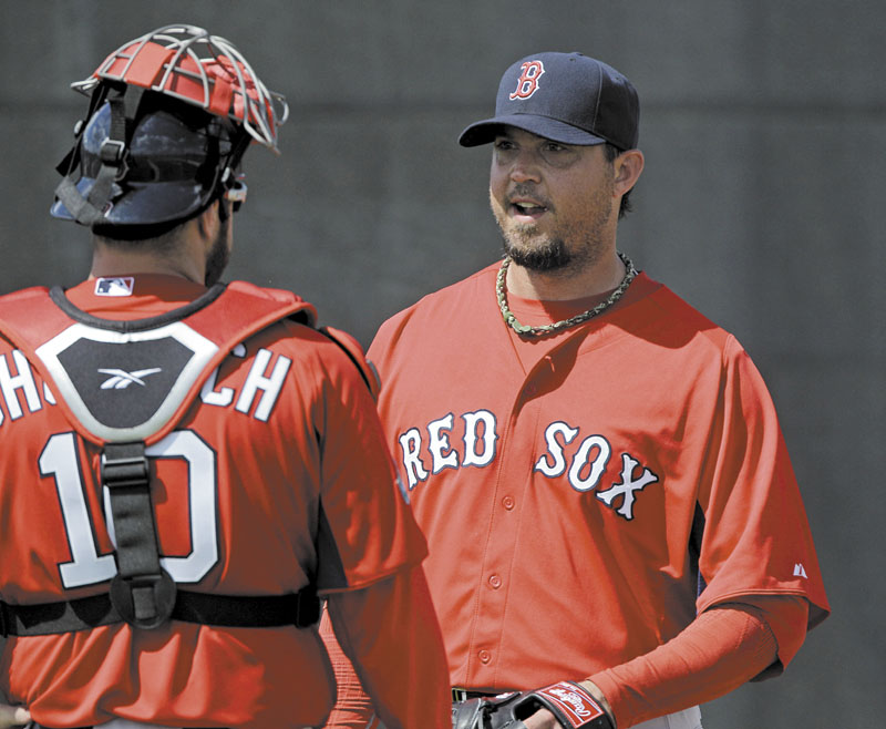 GETTING WORK DONE: Boston Red Sox pitcher Josh Beckett, right, talks with catcher Kelly Shoppach after a bullpen session Tuesday in Fort Myers, Fla. New Red Sox manager Bobby Valentine has made Sox pitchers work on improving defensively this spring.