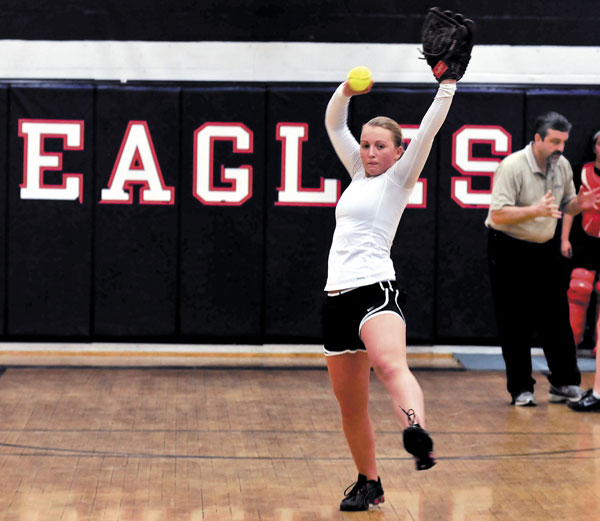 WARMING UP: Kai Smith, a starting pitcher for the Messalonskee High School softball team, throws during the team's first practice inside the gym Monday afternoon in Oakland. Eagles coach Leo Bouchard is at right.