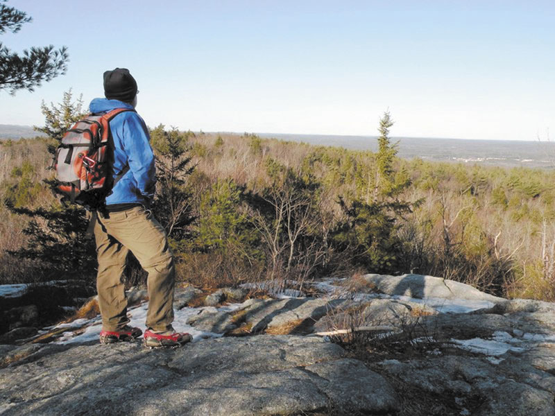 TAKING IN THE VIEW: From the top of Bauneg Beg's Middle Peak, hikers can see Pleasant Mountain and the White Mountains in the distance.