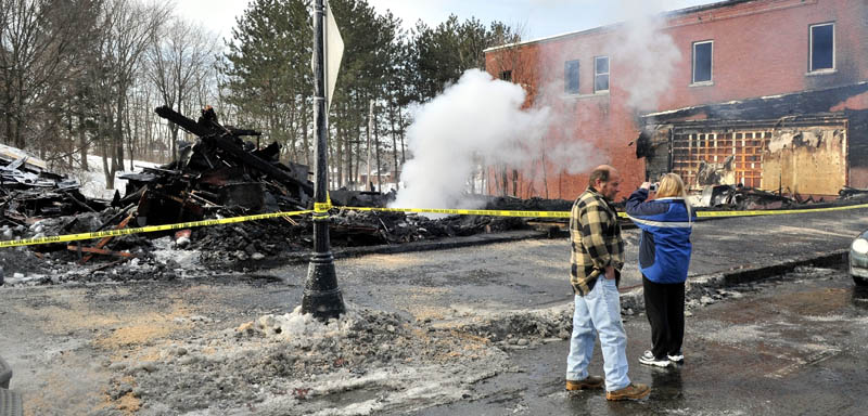 GONE: Nelson and Tracy Dube survey the scene on Wednesday of the still-smoldering remains of a building on Main Street in Madison that was destroyed by fire Tuesday night.
