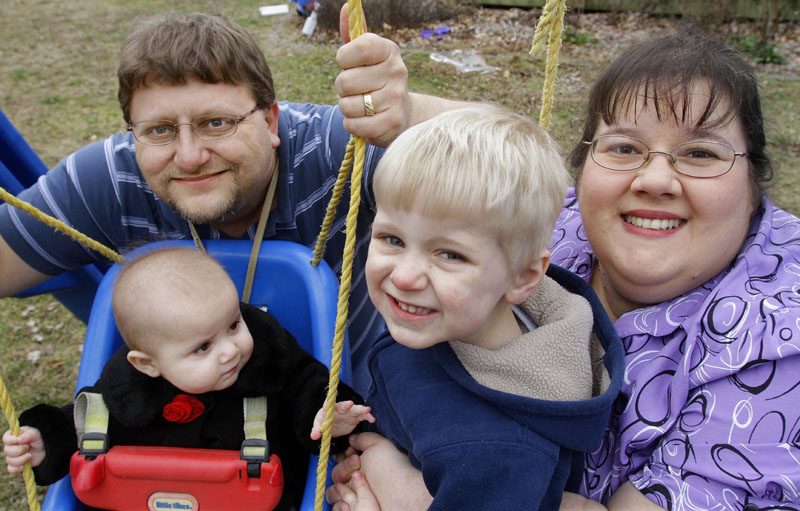 Nathen and Melissa Cobb pose for a photo last month with their two children Joshua, 3, and Savannah, 7 months, at their home in Riverton, Ill. The Cobbs tried to refinance their home last year but didn't qualify for the loan because of medical bills that had been sent to a collection agency. They were surprised because the bills had been paid. They now know that the collection action can stay on their credit report for seven years.