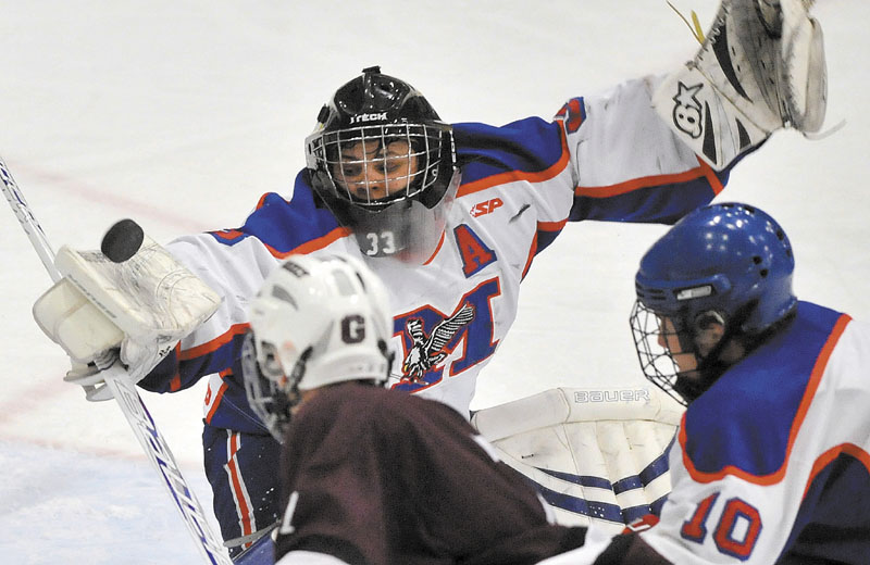 Photo by Michael G. Seamans Messalonskee High School goalie, Nate DelGiudace, 33, makes a blocker save against Greely High School in the second period of the Class B Boys hockey state championship game at the Colisee in Lewiston Saturday..
