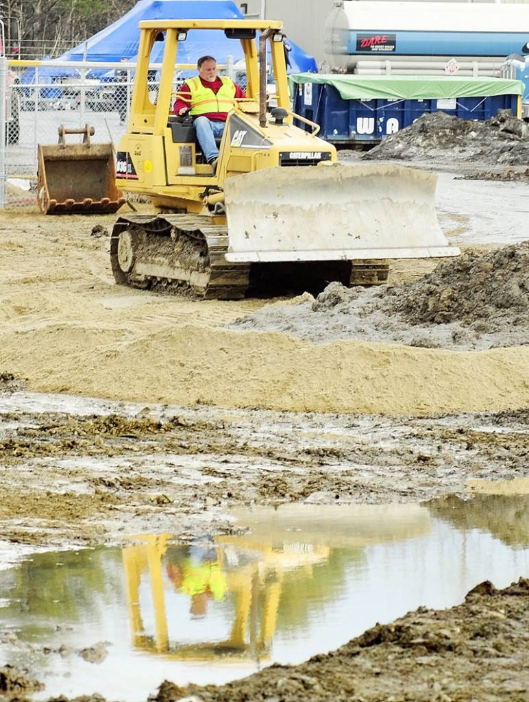 A worker operates a bulldozer at the oil spill cleanup site on Tuesday afternoon in Manchester.