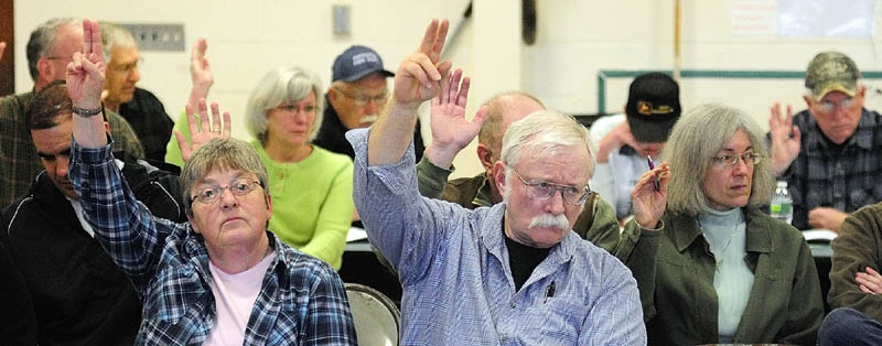 Residents vote for a question during the annual town meeting on Saturday morning at the Pittston School.