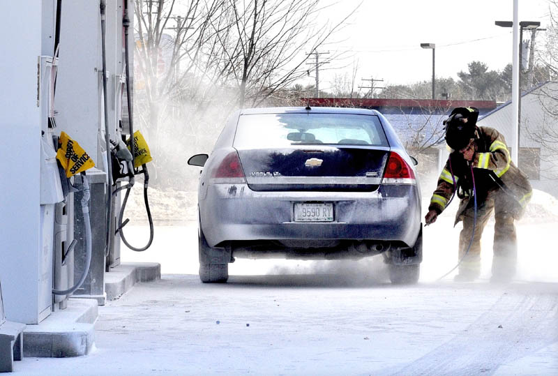 BLOW OUT: Skowhegan Fire Department Capt. Rick Caldwell wears protective gear while using an air hose to blow off fire suppressant powder that covered vehicles, customers and the ground at the Irving Circle K store in Skowhegan on Sunday.
