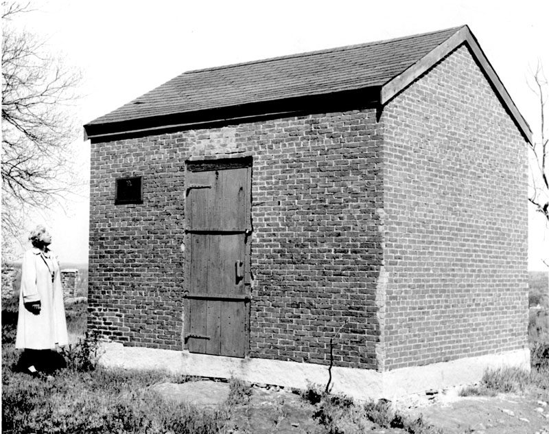 "Grace Maxwell looks at Hallowell's powder house, which was approved for construction around the time of the War of 1812 as a ""building of a magazine for the safe keeping of powder."" By June 1820, the powder house had been constructed and Ebenezer T. Warren conveyed the property it stood on to inhabitants of Hallowell."