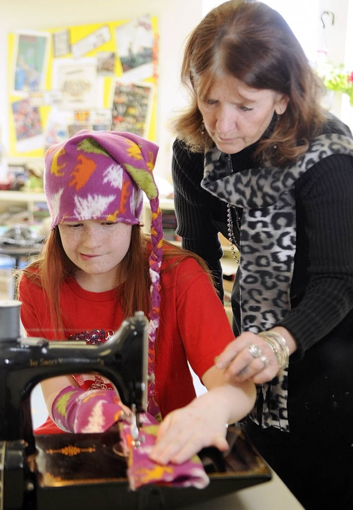 Brooklyn Hutchings sews one of her wristies with help from teacher Betsy Allen-McPhedran on Tuesday afternoon at Readfield Elementary School.