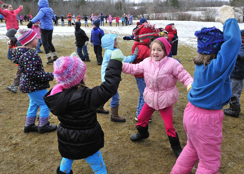 JUMPING JILLS: Bloomfield Academy students Delenn Travers, left front, and Elaine Vanadestine do jumping jack exercises during one of several outdoor events for WinterKids Wellness Day at the Skowhegan school on Thursday. Olympic gold medalist Seth Wescott spoke and encouraged kids to get outside and enjoy winter activity.