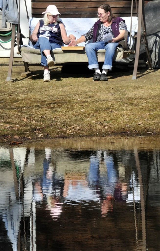 Jean Scripture, left, and Peggy Denis are reflected in a pond as they play a game of Yahtzee on a sunny and comfortable Monday. Spring officially arrived early this morning, and with more warm weather forecast for this week, the days for the seasonal pond may be numbered.