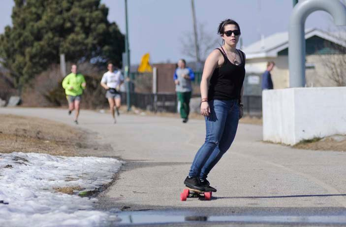 Lauren Collins of Portland takes advantage of today's warm weather by skateboarding along the Eastern Prom Trail in Portland. Collins is a student at Maine College of Art and had some free time before her next class.