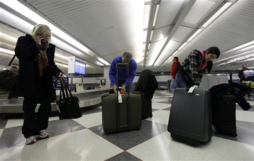 Travelers check their luggage at an United Airlines baggage claim area at O'Hare International Airport in Chicago.