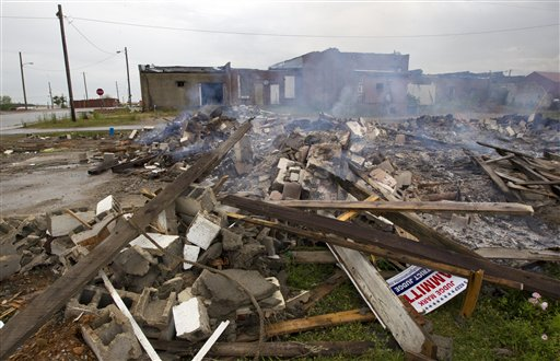 Tornado debris is burned in downtown Hackleburg, Ala., on Monday. It was about 3:20 p.m. a year ago when the skies grew dark over the northwest Alabama town of Hackleburg and a tornado dropped from the sky. When it left, 18 people were dead. All but one of town's 32 commercial buildings was wiped out, including its largest employer, leaving most of the survivors without jobs.
