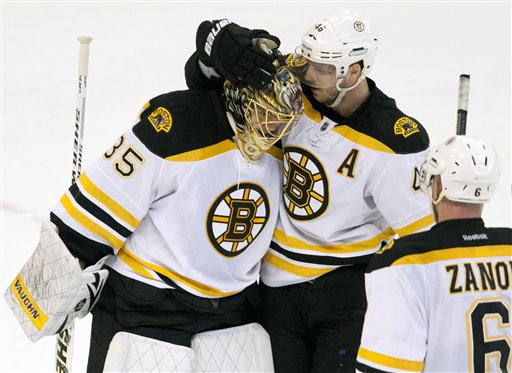 Boston Bruins center David Krejci, top right, congratulates goalie Anton Khudobin as Greg Zanon (6) looks on following the final whistle to end NHL hockey game action against the Ottawa Senators in Ottawa, Ontario, Thursday, April 5, 2012. The Bruins won 3-1. (AP Photo/The Canadian Press, Adrian Wyld) Canada;Canadian;sports;play;ice hockey;game;action;competitive;competition;compete;athletics;athletic;athlete;National;League;hockey;NHL