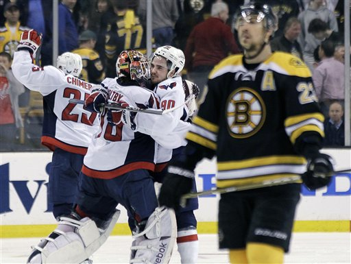 Boston Bruins center Chris Kelly (23) skates away as Washington Capitals goalie Braden Holtby (70); center Marcus Johansson (90), of Sweden; and left wing Jason Chimera (25) celebrate the Capitals' 2-1 win in overtime in Game 7 of an NHL hockey Stanley Cup first-round playoff series, in Boston on Wednesday, April 25, 2012. (AP Photo/Elise Amendola)