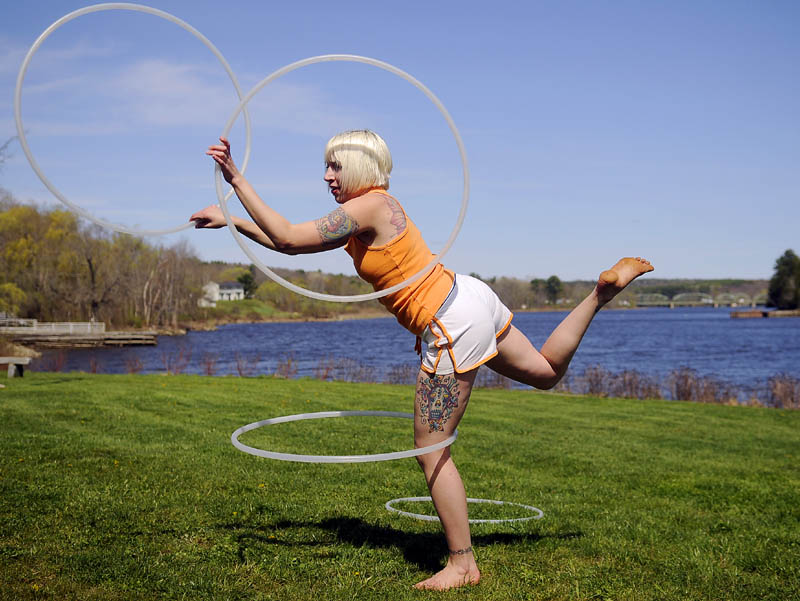 Alexis Golubow, of Richmond, rehearses her hula hoop performance Thursday at the park on the Kennebec River in Richmond. Golubow, who performs professionally, said frequent practice is warranted to twirl as many as four ovals at once.