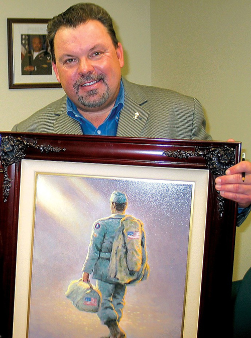 """In this October 2005 photo, Thomas Kinkade holds the painting """"Coming Home,"""" depicting an American service member walking into an """"ethereal"""" background. Kinkade created the painting based on a painting he did years earlier, also called """"Coming Home,"""" which depicted a soldier coming home for Christmas. """"I took the same soldier from that painting and recreated him in a setting much more ethereal so that it wasn't a specific home because people come home to all sorts of homes. You see the soldier walking into the field of mist, and ... it could ... suggest the homecoming of soldiers who pay the ultimate price overseas or it could be the soldier who is coming home to a future — his future — which is always a mystery."""" (Source: Wikipedia)"""