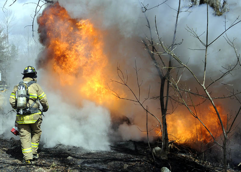 A firefighter approaches a burning fuel storage tank Tuesday after it exploded in Manchester, injuring Edward Bishop of Oakland. Bishop, who suffered serious burns, was listed in fair condition Wednesday at Maine Medical Center in Portland.